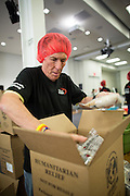 "SanDisk employee Jeff Orloff places sealed food bags into boxes for international shipping during the Stop Hunger Now Foundation's ""Mayday, Mayday"" food-packing event at SanDisk Corporation in Milpitas, California, on May 13, 2014. (Stan Olszewski/SOSKIphoto)"