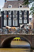 Tourists in horse drawn carriage cross bridge at Herengracht / Singel in Jordaan District, Amsterdam