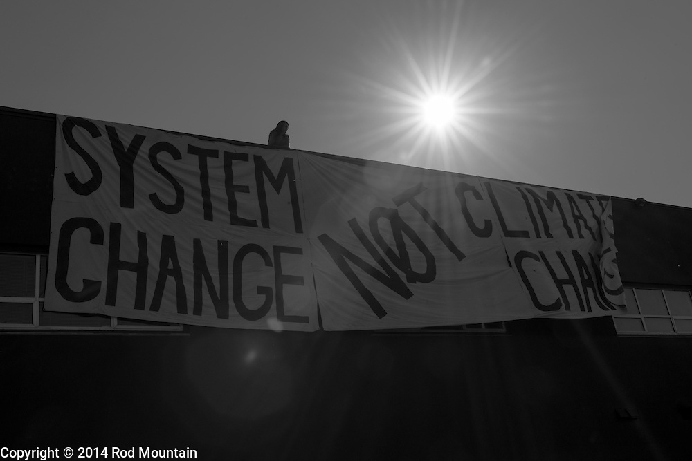 """The hot afternoon sun shines on as a man unveis a banner for the """"Party Against the Pipelines"""" Protest in Vancouver, B.C. Photo: © Rod Mountain"""