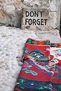 A sign saying 'don't forget' and some colourful carpets displayed for sale on The busy old market bazaar street Kujundziluk near the old bridge. Historic town of Mostar. Federation Bosne i Hercegovine. Bosnia Herzegovina, Europe.