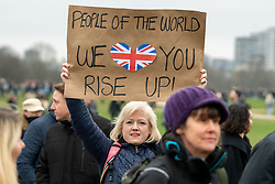 © Licensed to London News Pictures. 20/03/2021. London, UK. A woman holds up a placard as a people walk through Hyde Park during the anti-lockdown demonstration 'Worldwide Rally For Freedom' held in central London. Photo credit: Peter Manning/LNP
