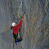 BAFFIN ISLAND, NUNAVUT, CANADA. Alex Lowe (MR) makes difficult hook moves, aid climbing high on Great Sail Peak, an Arctic big wall rock climb.