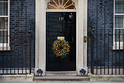 London, UK. 2 December, 2019. A Christmas wreath hangs from the door of 10 Downing Street.