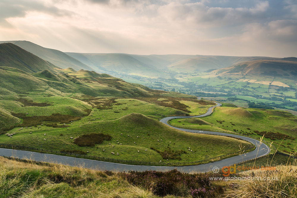 The road to Edale winds spectacularly around the remnants of Rushup Edge's landslip, as seen from the western slopes of Mam Tor. Kinder Scout can be seen on the horizon to the right, above the Vale of Edale. Late summer / early autumn in Derbyshire's Peak District. September, 2014.