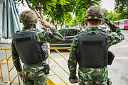 21 AUGUST 2014 - BANGKOK, THAILAND: Thai soldiers salute as a member of the National Legislative Assembly (NLA) enters the parliament complex. The NLA met Thursday to select the new Prime Minster. The NLA was hand picked by the Thai junta, formally called the National Council for Peace and Order (NCPO), and is supposed to guide Thailand back to civilian rule after a military coup overthrew the elected government in May. The NLA unanimously selected General Prayuth Chan-ocha, commander of the Thai Armed Forces and leader of the coup in May that deposed the elected civilian government, as Prime Minister. Prayuth is Thailand's 29th Prime Minister since the 1932 coup that created Thailand's constitutional monarchy.      PHOTO BY JACK KURTZ