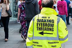 A man wearing a hi-viz jacket advertising beauty treatments. UK