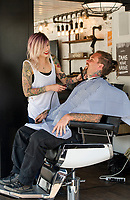 Justine Ferrell of Austin, TX gives Yohann Corbus of Quebec, Canada a beard trim at Flo's Chop Shop at the Progressive Insurance booth on Lakeside Avenue Thursday afternoon.  (Karen Bobotas/for the Laconia Daily Sun)