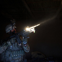 A British soldier of 16 Air Assault Bde's elite BRF (Brigade Reconnaissance Force) uses his weapon mounted flashlight to scan a room as the troops move from compound to compound searching for weapons and explosives as part of an operation in the Western Dasht, Helmand Province, Southern Afghanistan on the 18th of March 2011.