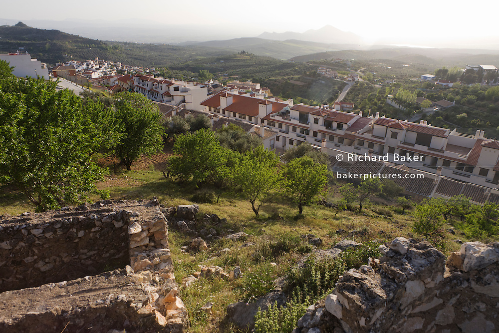 New housing and ruined walls on hillside in rural Andalucia.