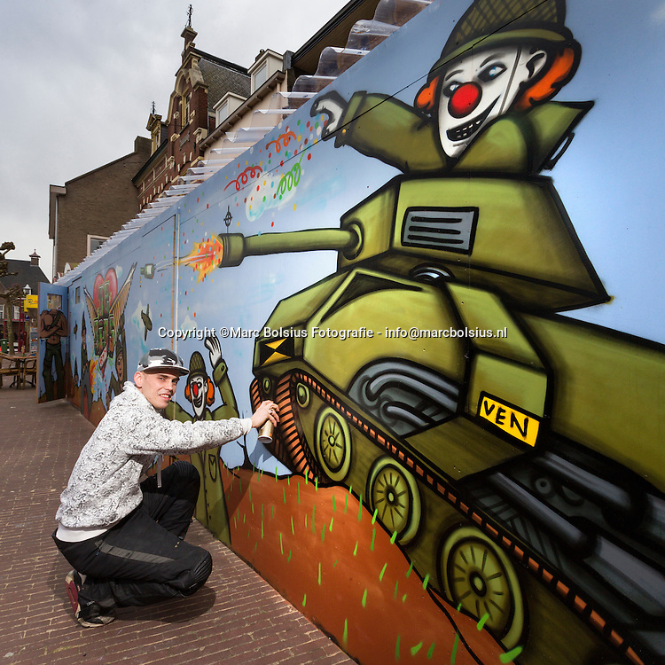 Nederland, Boxtel, graffiti kunstenaar Steven van de Ven werkend aan zijn carnavalsafbeelding bij cafe het Hart van Boxtel op de  markt.
