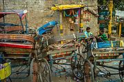 Rickshaw wallahs rest and chat amongst their vehicles in Sadar Bazaar, Delhi, India.