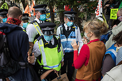 London, UK. 4th September, 2020. Extinction Rebellion co-founder Dr Gail Bradbrook tries to reason with Metropolitan Police officers moving in to seize a sound system being used by activists from HS2 Rebellion to tell a children's story during a protest rally in Parliament Square. The rally, and a later protest action at the Department of Transport during which activists glued themselves to the doors and pavement outside and sprayed fake blood around the entrance, coincided with an announcement by HS2 Ltd that construction of the controversial £106bn high-speed rail link will now commence.