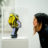 London, UK - 18 February 2013: a Tate employee looks at 'Head with Blue Shadow' during the  'Lichtenstein: A Retrospective' exhibition that opens at Tate Modern in London on the 21st of February. The exhibition is the first major Lichtenstein retrospective for twenty years, bringing together over 125 of the artist's most definitive paintings and sculptures. Built on new research and scholarship, the exhibition reassesses Lichtenstein's work and his enduring legacy.