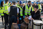Air passengers find their way through environmental activists protesting about Climate Change during the occupation of City Airport (London's Business Travel hub) in east London, the fourth day of a two-week prolonged worldwide protest by members of Extinction Rebellion, on 10th October 2019, in London, England.