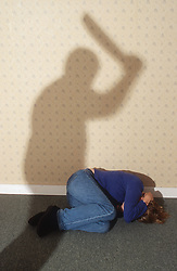 Young woman lying huddled on floor as abuser prepares to beat her with a stick,