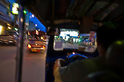 """29 JUNE 2011 - CHIANG MAI, THAILAND: Riding in a """"tuk-tuk"""" or three wheeled taxi, in Chiang Mai, Thailand. Tuk-tuks are common throughout Asia. They are called tuk-tuk because of the distinctive sound their two-stroke motors make. PHOTO BY JACK KURTZ"""