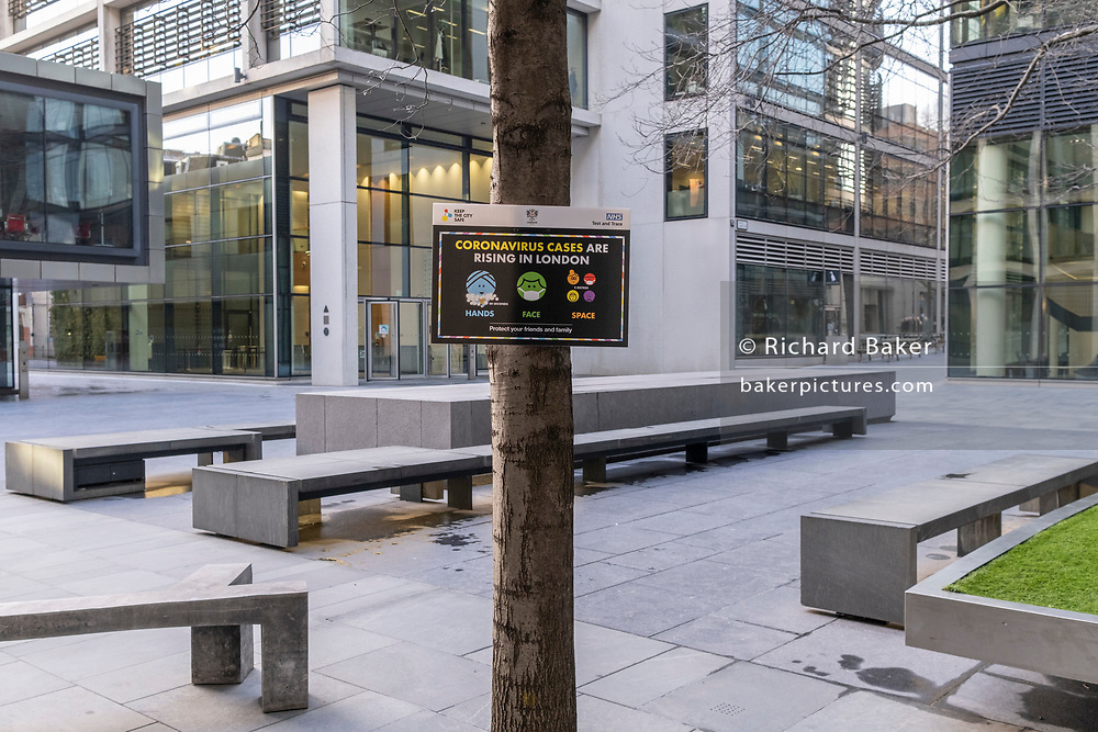 Although Londoners largely remain working at home, a government NHS (National Health Service) sign placed on a tree in an empty plaza, advises Londoners about another rise in Covid infections, during the third lockdown of the Coronavirus pandemic, in the 'City of London', the capital's financial district, aka The Square Mile, on 2nd February 2021, in London, England.