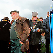 Spectator wearing barbour jackets and flat caps standing by the betting kiosks at the Tiverton Staghounds point-to-point steeplechases at Bratton Down, Barnstaple, Devon, UK. Fundraiser for the Devon and Somerset Staghounds.