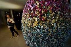 © Licensed to London News Pictures. 22/01/2011 London, UK. A guest looks at a giant egg designed by fashion designer Mary Katrantzou in the lobby of The May Fair Hotel, London. The egg is one of 200 hidden around the capital. Egg hunters who find them are in with the chance of winning a Faberge egg worth £100,000..Photo credit : Simon Jacobs/LNP