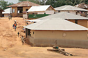 People walk through the village of Julijuah, Bomi county, Liberia on Tuesday April 3, 2012.