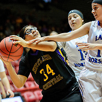 031015  Adron Gardner/Independent<br /> <br /> Kirtland Central Bronco DD Begay (34), left,  sights a shot under pressure from St. Michael's Horsemen Briona Vigil  (10) during the New Mexico state basketball tournament at The Pit in Albuquerque Tuesday.