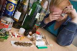 Upset woman on the phone surrounded by a selection of drugs and alcohol,