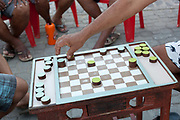 Detail shot of middle aged Brazilian Bahian men playing draughts checkers in the street in Cachoeira, Bahia.