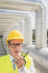 Young engineer talking with walkie-talkie at geothermal power station, Bavaria, Germany