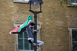 London, UK. 11th May, 2021. A demonstrator climbs a lamp post with a Palestinian flag as thousands of people attend an emergency protest in solidarity with the Palestinian people organised outside Downing Street by Palestine Solidarity Campaign, Friends of Al Aqsa, Stop The War Coalition and Palestinian Forum in Britain. The rally took place in protest against Israeli air raids on Gaza, the deployment of Israeli forces against worshippers at the Al-Aqsa mosque during Ramadan and attempts to forcibly displace Palestinian families from the Sheikh Jarrah neighbourhood of East Jerusalem.