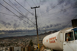 A water truck makes its way into the poor, dangerous neighborhoods of Nogales where most residents have to steal electricity and have no running water.