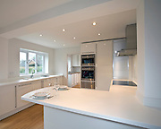 white kitchen breakfast bar in white kitchen with wooden floor