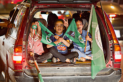 © Licensed to London News Pictures. 27/04/2014. Sulaimaniya, Iraq.  Children wave flags linked to the Patriotic Union of Kurdistan (PUK) political party flash from the back of a car during celebrations in the lead up to the 2014 Iraqi parliamentary elections in Sulaimaniya, Iraqi-Kurdistan..<br /> <br /> Although banned in other parts of Iraqi-Kurdistan, the days leading up to an election in Sulaimaniya sees political supporters of all the three main parties parading up and down the main street of the city, waving flags, honking horns, letting off fireworks and firing pistols and rifles into the air.<br /> <br /> The period leading up to the elections, the fourth held since the 2003 coalition forces invasion, has already seen six polling stations in central Iraq hit by suicide bombers causing at least 27 deaths. Photo credit: Matt Cetti-Roberts/LNP