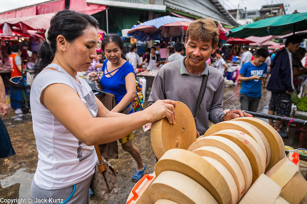 """24 AUGUST 2013 - BANGKOK, THAILAND:     A man sells cutting boards from a cart in Khlong Toei Market in Bangkok. Thailand entered a """"technical"""" recession this month after the economy shrank by 0.3% in the second quarter of the year. The 0.3% contraction in gross domestic product between April and June followed a previous fall of 1.7% during the first quarter of 2013. The contraction is being blamed on a drop in demand for exports, a drop in domestic demand and a loss of consumer confidence. At the same time, the value of the Thai Baht against the US Dollar has dropped significantly, from a high of about 28Baht to $1 in April to 32THB to 1USD in August.    PHOTO BY JACK KURTZ"""