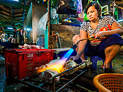 08 JUNE 2017 - BANGKOK, THAILAND: A worker uses a blow torch to scorch the hair off of a pork leg in Khlong Toey Market, Bangkok's main fresh market. Thai consumer confidence dropped for the first time in six months in May following a pair of bombings in Bangkok, low commodity prices paid to farmers and a sharp rise in the value of the Thai Baht versus the US Dollar and the EU Euro. The Baht is surging because of political uncertainty, related to Donald Trump, in the US and Europe. The Baht's rise is being blamed for a drop in Thai exports. This week the Baht has been trading at around 33.90 Baht to $1US, it's highest point in two years.      PHOTO BY JACK KURTZ