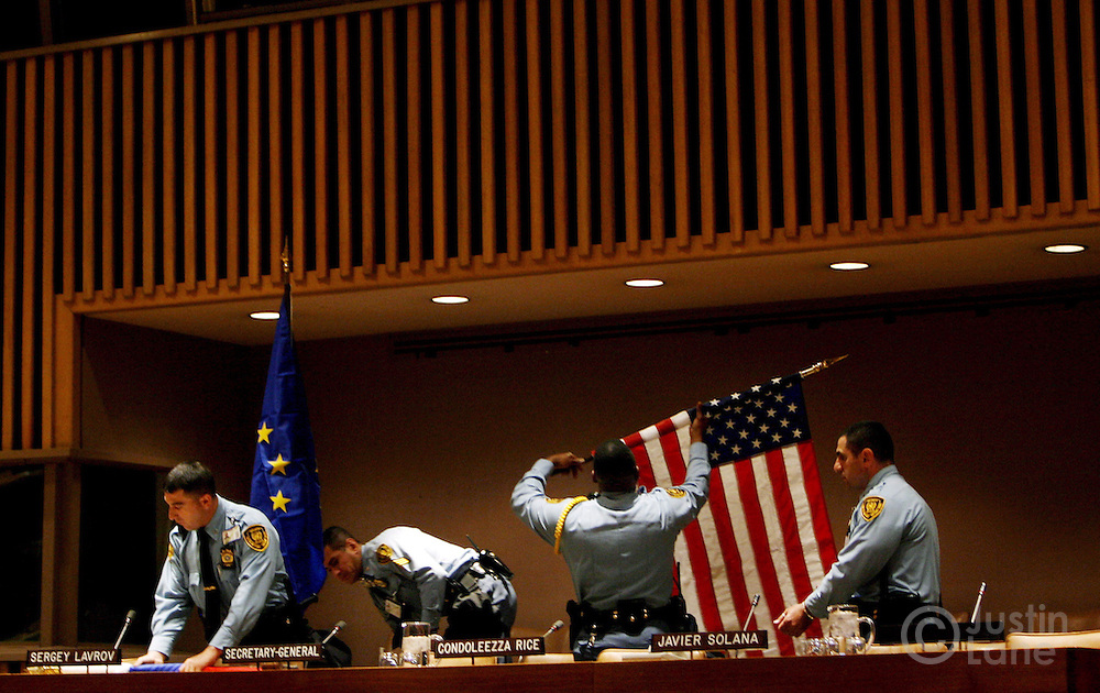 epa00709106 United Nations Police Officers roll up national flags after a press conference with, among others, US Secretary of State Condoleezza Rice and UN Secretary-General Kofi Annan at United Nations Headquarters Tuesday, 9 May 2006 in New York. Foreign Ministers from the five permanent member countries on the United Nations Security Council are in New York to discuss a number of international issues including Darfur and the nuclear situation in Iran.  EPA/JUSTIN LANE
