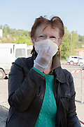 woman adjusting her mask with gloved hand during Covid 19 crisis and lockdown France Limoux April 2020