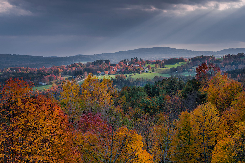 Fall color trees foreground and light striking hillside homes, farms, and church steeple, Peacham, VT