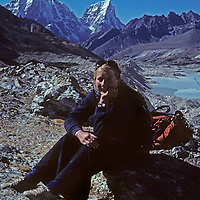 A trekker relaxes in Nepal's Imja Valley, beside the Imja Glacier and its glacial outflow lakes.  Behind her are [Mounts] Taweche and Cholatse.