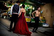 Hong Kong, China - Woman in a red velvet evening dress standing in a street with her boyfriend on May 01, 2018.Hong Kong, Chine - Femme en robe du soir en velours rouge debout dans une rue avec son petit ami le 1er mai 2018.
