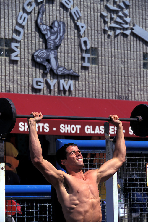 """Men pump iron at the famed Muscle Beach, also knows as """"the pit"""", along the boardwalk at Venice Beach in Los Angeles, Ca."""