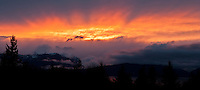 crepuscular rays light the clouds above the Olympic Mountains at sunset viewed from the Kitsap Peninsula in Puget Sound, Washington, USA panorama