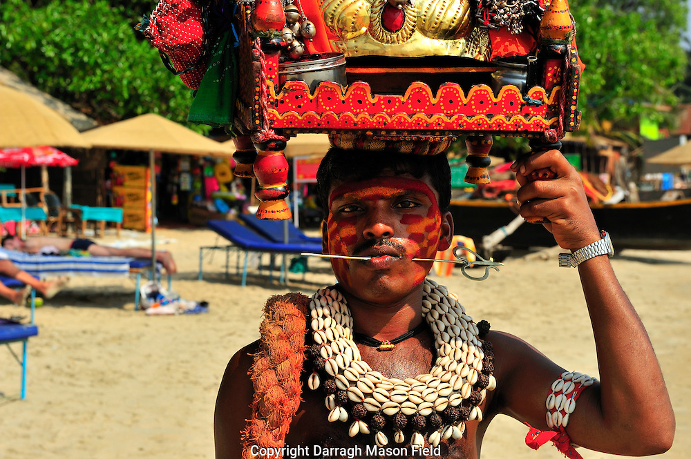 Man on palolem beach with a spike through his cheek for his religious beliefs.  He visits businesses where they give him cash for good luck.
