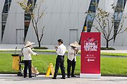 Grounds crew stands near a sign at a event promoting the 11.11 shopping festival at the Alibaba Group Holding Ltd. headquarters in Hangzhou, China, on Tuesday, Oct. 13, 2015.