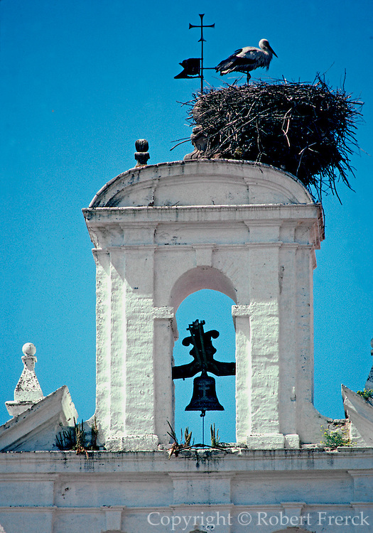 SPAIN, ANDALUSIA, CORDOBA a stork's nest perched on a church belltower in the old Moorish part of the city