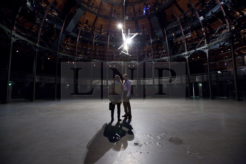 © Licensed to London News Pictures. 31/07/2013. London, UK. Visitors to London's Roundhouse view 'Timepiece', a large scale light installation by British artist Conrad Shawcross, at the press view for Bloomberg's Summer at the Roundhouse in London today (31/07/2013). The specially commission piece, which was created in response to the Roundhouse's iconic main space using its 24 pillars to mark the hours of the day, forms part of of Bloomberg's 'Summer at the Roundhouse' and will be open to the public from the 1st to the 25th of August 2013. Photo credit: Matt Cetti-Roberts/LNP