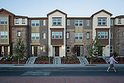 A man walks past completed town homes at the Taylor Morrison town home project on the 1500 block of McCandless Drive in Milpitas, California, on July 21, 2014. (Stan Olszewski/SOSKIphoto)