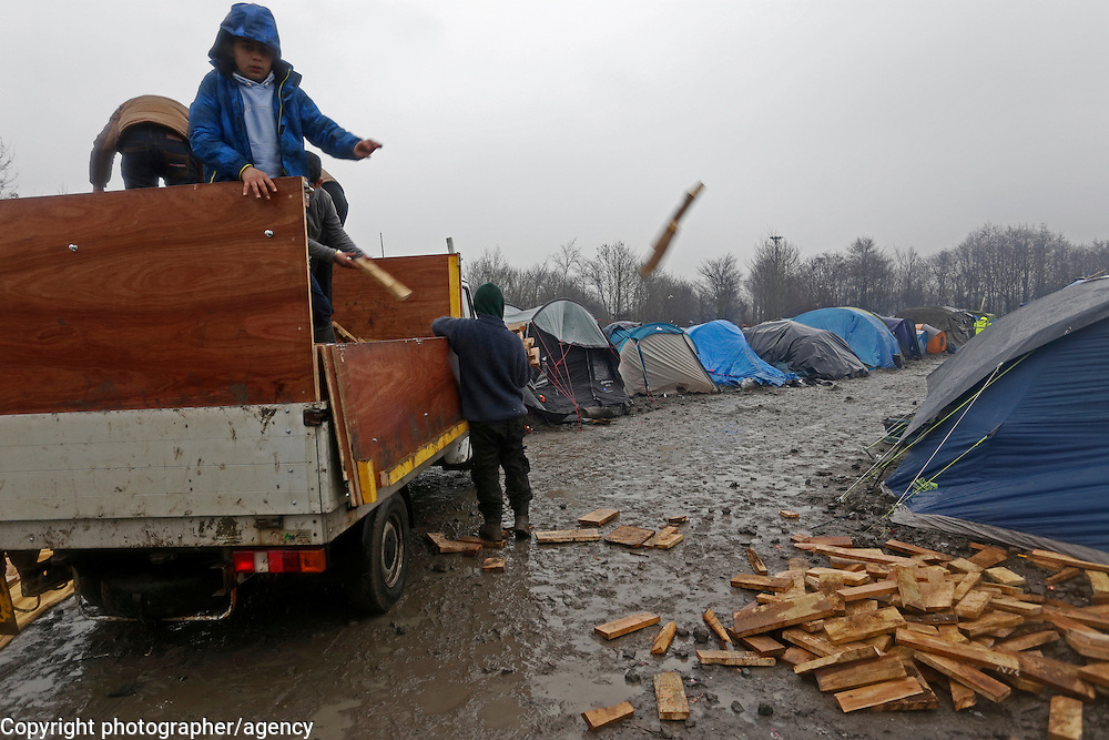 Firewood is distribuetd from a truck, 22 January  in the Grande-Synthe refugee camp, near Dunkirk in northern France.