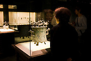 Visitor looks at bronze cowrie container on display in glass case at the Shanghai Museum, China