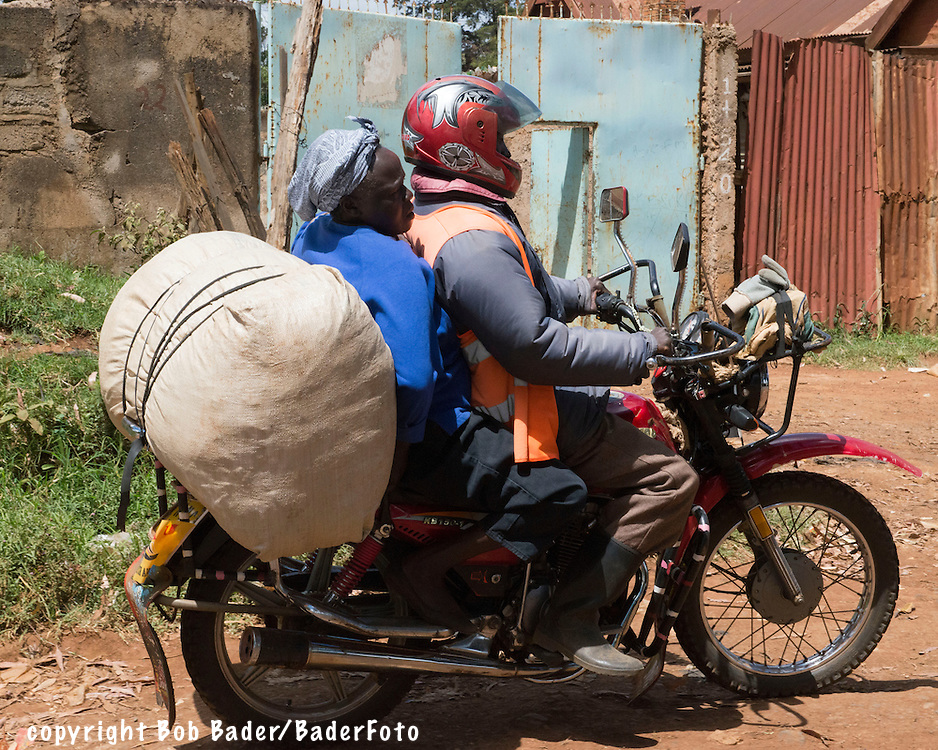 Woman on a Boda Boda (taxi) in Eldoret, Kenya with large bag of charcoal