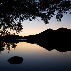 Sunset and the Percy Peaks reflect in Christine Lake in Stark, New Hampshire.